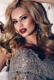 Mujer magnífica con el pelo rubio y el maquillaje brillante, vestido lujoso de la lentejuela que lleva Imagen de archivo libre de regalías