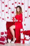 Mujer magnífica en el vestido rojo largo que se sienta en sitio adornado con Foto de archivo