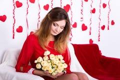 Mujer magnífica en el vestido rojo que se sienta en el sofá con las flores en deco Fotos de archivo libres de regalías
