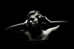 Mujer magnífica en escuchar blanco y negro la música Fotografía de archivo