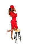 Mujer magnífica en vestido y casquillo rojos Fotos de archivo