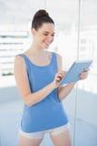 Mujer magnífica feliz en ropa de deportes usando la PC de la tableta Imagenes de archivo