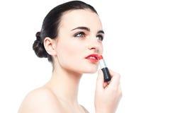Mujer magnífica joven que aplica el lápiz labial Imagenes de archivo