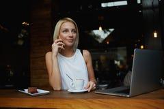 Mujer magnífica joven que tiene conversación telefónica elegante mientras que se sienta delante del ordenador portátil abierto en imagenes de archivo