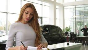 Mujer magnífica que compra un nuevo coche en la representación que sonríe a la cámara almacen de video
