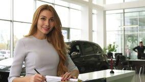 Mujer magnífica que compra un nuevo coche en la representación que sonríe a la cámara foto de archivo libre de regalías