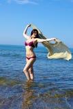 Mujer magnífica que juega con velo en el agua que se divierte con el viento Imagen de archivo