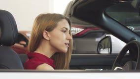 Mujer magnífica que presenta en su nuevo descapotable que lleva a cabo llaves del coche almacen de video