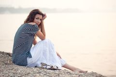 Mujer magnífica que se sienta en la playa Foto de archivo libre de regalías