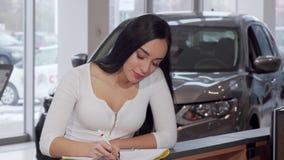 Mujer magnífica que sonríe a la cámara, papeles de firma después de comprar el nuevo coche metrajes