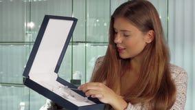 Mujer magnífica que sonríe, mientras que elige un collar costoso en la joyería almacen de video