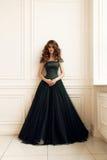 Mujer magnífica con maquillaje del pelo oscuro y de la tarde en el vestido elegante que presenta en estudio Fotografía de archivo