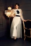 Mujer magnífica con maquillaje del pelo oscuro y de la tarde en el vestido elegante que presenta en estudio Fotos de archivo libres de regalías
