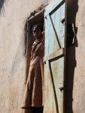 Mujer malgache que mira fuera del umbral imagenes de archivo
