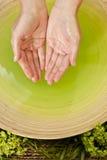 Mujer \ \ \ 'manos de s en líquido verde en el balneario de la salud Imágenes de archivo libres de regalías