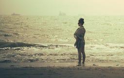 Mujer maravillosa que se coloca en la playa con puesta del sol Foto de archivo