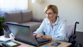 Mujer mayor acertada en la silla de ruedas que trabaja en el ordenador portátil, charlando con el cliente almacen de metraje de vídeo