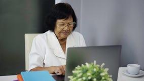 Mujer mayor acertada que trabaja en el ordenador portátil con los brazos aumentados almacen de video
