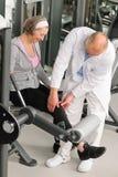 Mujer mayor activa de la ayuda del fisioterapeuta en la gimnasia Fotografía de archivo