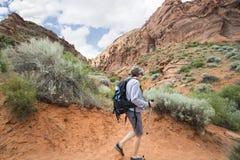 Mujer mayor activa que camina en un barranco rojo hermoso de la roca Fotografía de archivo libre de regalías