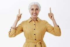 Mujer mayor activa y feliz activada con el pelo blanco en la capa amarilla elegante que aumenta los dedos índices que destaca y imagenes de archivo