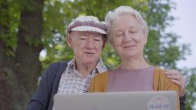 Mujer mayor adorable del retrato con el pelo gris y el viejo hombre en el casquillo que se sienta en el banco en el parque hermos almacen de video