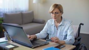 Mujer mayor agradable en número de tarjeta de la silla de ruedas que mecanografía en el ordenador portátil, cuentas que pagan almacen de metraje de vídeo