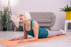 Mujer mayor agradable que ejercita los músculos de su cuello imagen de archivo