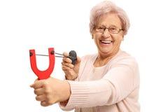 Mujer mayor alegre que apunta con una catapulta y una roca Fotografía de archivo libre de regalías