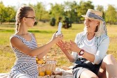 Mujer mayor alegre que disfruta de comida campestre con su abuela agradable Foto de archivo