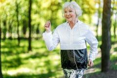 Mujer mayor alegre que disfruta del funcionamiento en bosque imagen de archivo