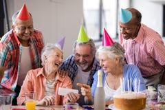 Mujer mayor alegre que muestra el teléfono móvil a los amigos en partido Imagen de archivo