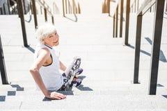 Mujer mayor alegre que se relaja después de entrenar en las escaleras imagenes de archivo
