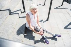 Mujer mayor alegre que se relaja mientras que ejercita en las escaleras al aire libre fotos de archivo libres de regalías