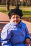 Mujer mayor alegre que se sienta con un palillo Foto de archivo libre de regalías