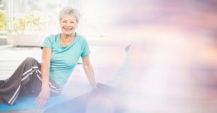 Mujer mayor apta que ejercita en clase de la yoga Foto de archivo