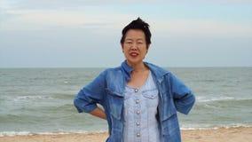 Mujer mayor asiática confiada elegante en los vaqueros Jumper At Ocean almacen de metraje de vídeo