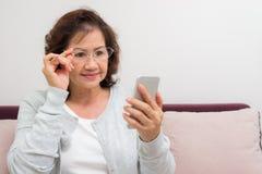 Mujer mayor asiática feliz que recibe el nuevo mensaje en su teléfono Foto de archivo