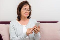 Mujer mayor asiática que mira a través de sus contactos imagen de archivo libre de regalías