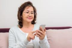 Mujer mayor asiática que mira a través de sus contactos imagen de archivo
