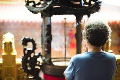 Mujer mayor asiática que ruega a Buda Imagen de archivo libre de regalías