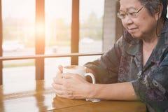 mujer mayor asiática que se sienta y que descansa en cafetería del café con Fotos de archivo