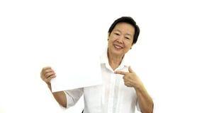 Mujer mayor asiática feliz que lleva a cabo la muestra en blanco blanca en el CCB del aislante Imagenes de archivo