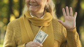 Mujer mayor astuta que sostiene el dinero, estado de engaño, consiguiendo el beneficio social doble metrajes