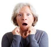 Mujer mayor asustada dada una sacudida eléctrica foto de archivo