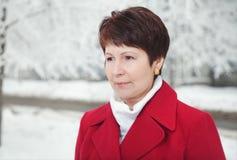 Mujer mayor atractiva en la calle nevosa del invierno Imágenes de archivo libres de regalías