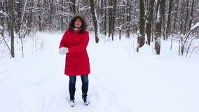 Mujer mayor atractiva en la madera de la nieve del invierno en la capa roja que se divierte almacen de video