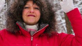 Mujer mayor atractiva en la madera de la nieve del invierno en la capa roja que se divierte almacen de metraje de vídeo