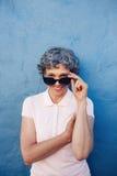 Mujer mayor atractiva que mira a escondidas sobre las gafas de sol Foto de archivo libre de regalías