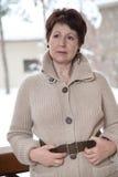 Mujer mayor atractiva que presenta en terraza al aire libre en invierno Imagen de archivo libre de regalías